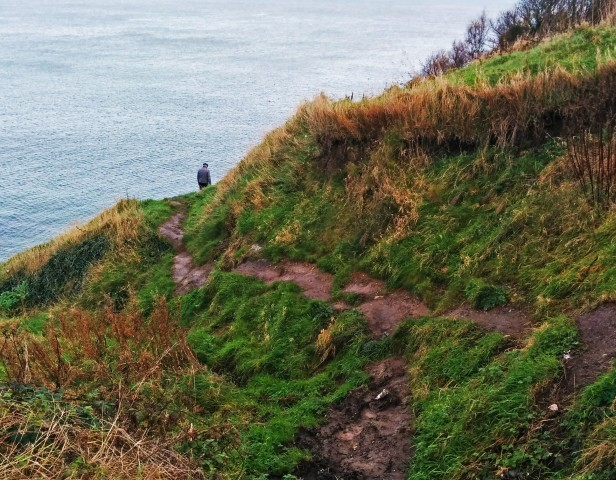 """Old man looking out to the sea"" -- man walking alone on the Cliff Path Loop"